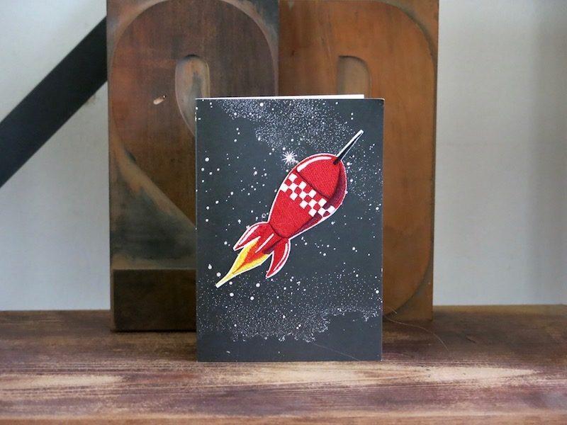 Une carte postale bazartherapy avec un écusson en cadeau à offrir