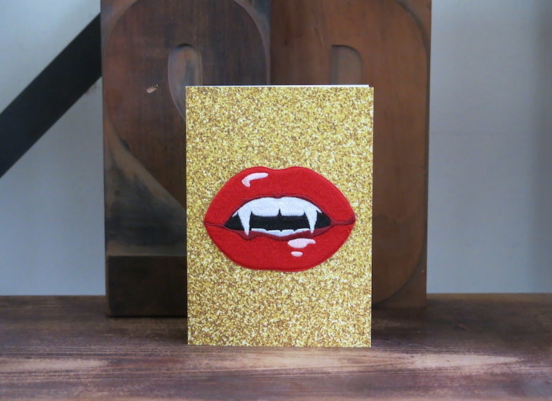 Une carte postale bazartherapy avec un écusson à offrir en cadeau